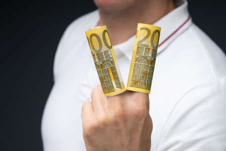 Close-up Of A Man's Hand Showing Rolled Up Two Hundred Euro Banknotes Over His Fingers Stock fotó - 133704997