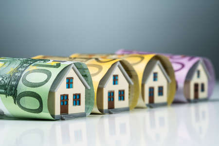 Row Of Miniature Houses Inside The Euro Banknotes On White Desk Against Gray Background Stock fotó - 133704998