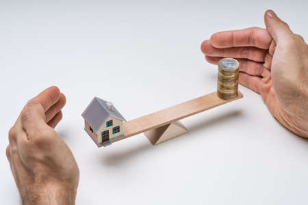Mans Hand Protecting The Balance Of House And Stack Of Coins On Seesaw Reklamní fotografie