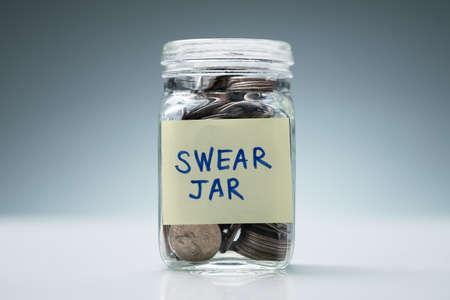 Close-up d'un bocal en verre avec Jure Jar texte rempli de pièces contre l'arrière-plan gris Banque d'images