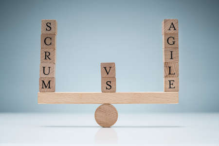 Balance Of Wooden Scrum Vs Agile Blocks On Seesaw Over The Desk Against Blue Background