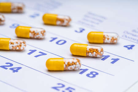 Close-up Of Yellow Transparent Capsules On Calendar Dates Фото со стока