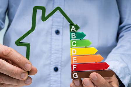 Mid Section Of A Person's Hand Holding Green House Energy Efficiency Graph Stock fotó - 133705059