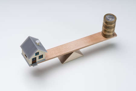 Stacked Of Coins And Miniature House On Wooden Seesaw Against White Background