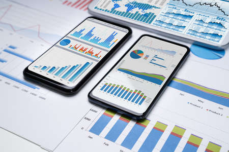 Close-up Of Financial Graphs On Screens Of Multiples Smartphones On Desk Stock fotó - 133705064