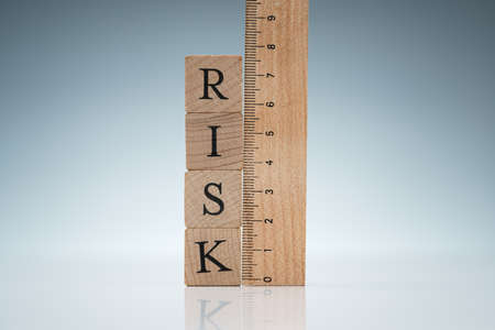 Risk Word On Wooden Blocks Stacked Near The Ruler On Reflective Desk