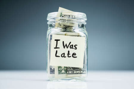 Dollar Banknotes In The Jar With Adhesive Notes Written I Was Late On White Desk