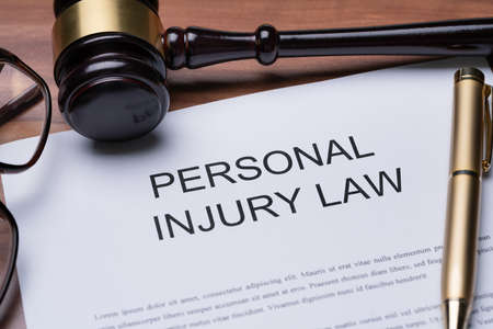 Spectacles And Pen On Paper Of Personal Injury Law Over Desk 스톡 콘텐츠