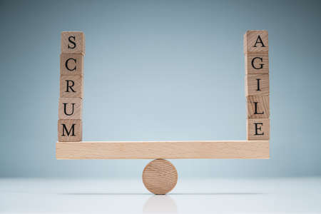 Stack Of Wooden Scrum And Agile Blocks On Seesaw Over The White Desk