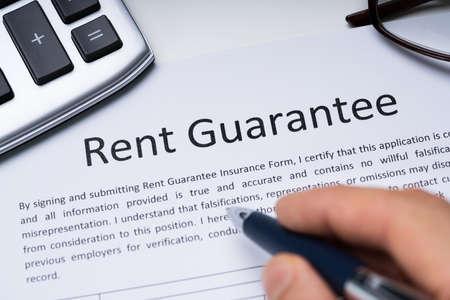 Persona que llena el formulario de garantía de alquiler sosteniendo la pluma en el escritorio con calculadora y gafas