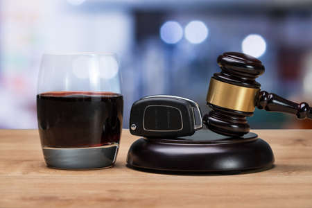 Car Key And Gavel Over Striking Block Near Glass Of Alcohol In Court Room