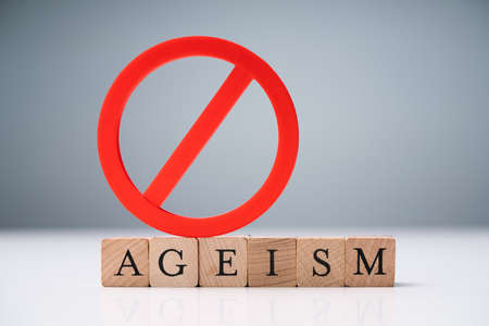 Ageism Text On Round Wooden Blocks Over Reflective White Desk Reklamní fotografie