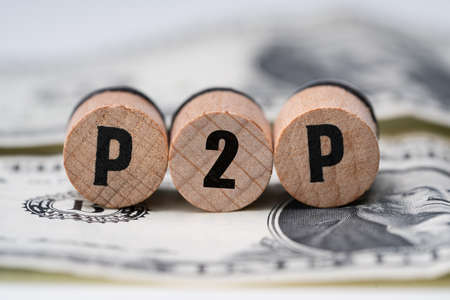 Close-up Of A P2p Word On Round Wooden Blocks Over Dollar Bill Stock fotó - 133705155