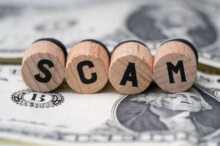 Close-up Of A Scam Word On Round Wooden Blocks Over Dollar Bill Stock fotó - 133705158