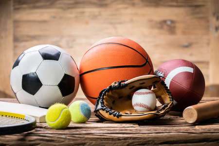 High Angle View Of Various Sport Accessories On Textured Wooden Surface