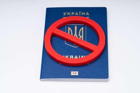 Close-up Of Red No Sign On Ukraine Passport Over White Desk Фото со стока