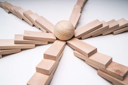 Close-up Of A Silver Ball In The Center Of Collapsed Wooden Dominoes Over White Backdrop 写真素材