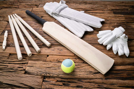 Elevated View Of Cricket Accessories And Tools On Brown Textured Backdrop Banco de Imagens