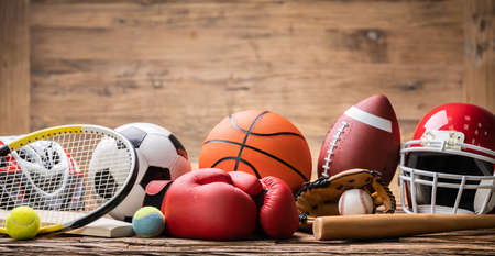 Close-up Of Various Sport Equipment On Textured Wooden Desk