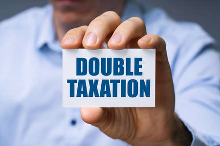 Man Showing Card With Double Taxation Text Stock Photo
