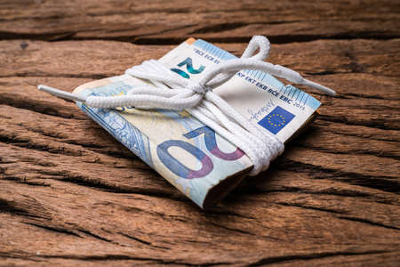 Bundle Of Euro Currency Banknotes Tied With White Lace Over Rough Wooden Textured Backdrop Stock fotó - 133705413