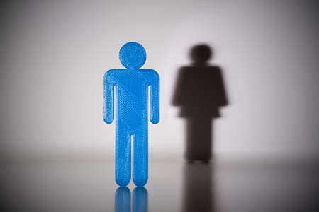 Blue Male Gender Human Figure With Shadow Of Female Gender Human Figure On Wall