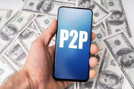Persons Hand Holding Mobile Phone With P2p Text Against Dollar Bills Background