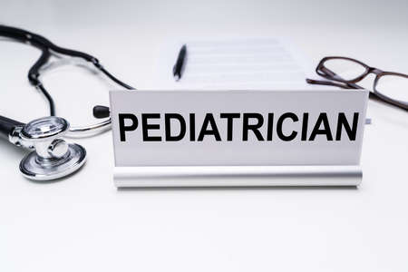 Pediatrician Job Title On Nameplate Over Desk With Spectacles And Stethoscope