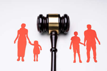 Separated Family Figure Paper Cutout And Judge Gavel Over White Surface