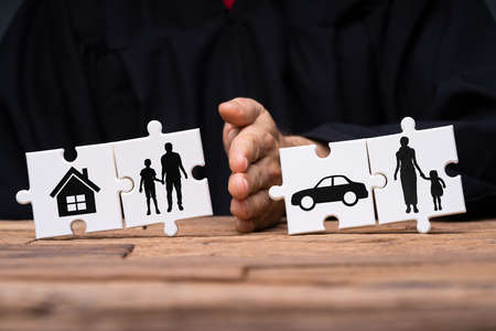 Jigsaw Puzzles Showing Separation Of Family With House And Car Divided By Persons Hand Stockfoto