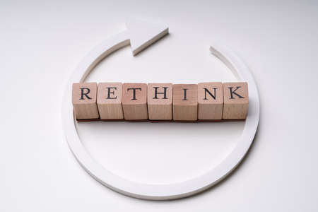 Close-up Of Rethink Word On Wooden Blocks Near White Directional Arrow Isolated Over White Background