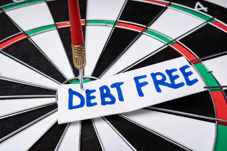 Close-up Of Handwritten Text Debt Free On Notepaper Stuck At The Center Of Dartboard