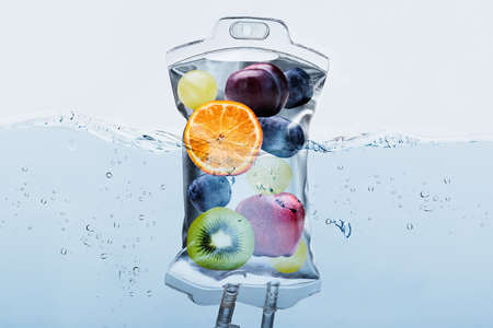 Close-up Of Various Fruit Slices In Saline Bag Dip In Water Against White Background Stockfoto