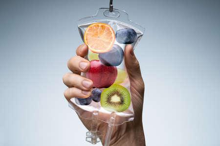 La mano della persona che tiene la sacca di soluzione fisiologica riempita con varie fette di frutta contro uno sfondo grigio