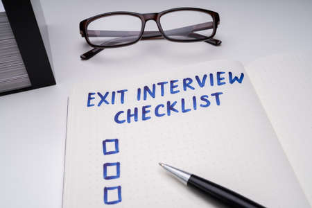 Handwritten Exit Interview Checklist Message On Notebook With Blue Marker And Spectacles Over Office Desk 版權商用圖片