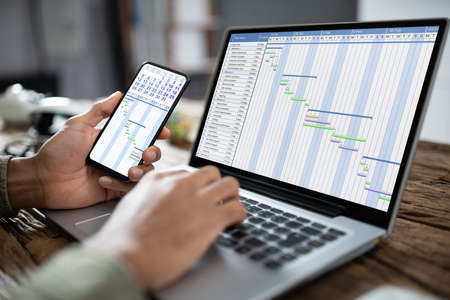 Close-up Of A Businessperson's Hand Using Smartphone While Analyzing Gantt Chart On Laptop Banco de Imagens
