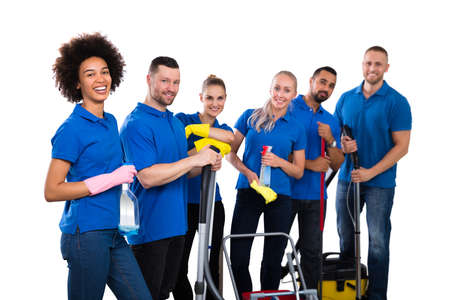 Smiling Multiethnic Group Of Janitors Wearing Blue T-shirt Standing Grouped Together With Their Equipment Foto de archivo - 134306765