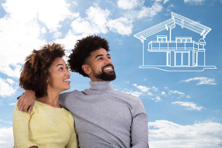 Smiling Portrait Of A Young Couple Dreaming Of The Drawn House Against Blue Sky Banque d'images
