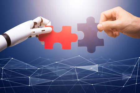 Robot And Man's Hand Joining The Red And Blue Jigsaw Pieces On Technology Background