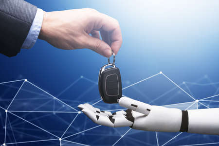 Close-up Of A Businessperson's Hand Giving Car Key To Robot On Blue Technology Background
