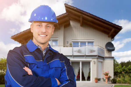 Confident Male Architect With His Arms Crossed Standing In Front Of House Looking At Camera