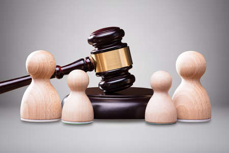 Wooden Pawns In Front Of Gavel And Mallet Against Gray Background