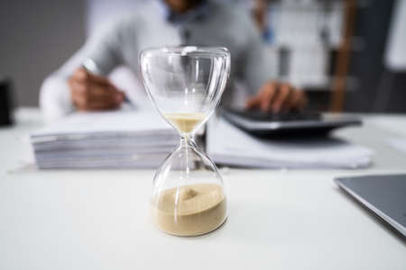 Close-up Of Hourglass In Front Of Businessperson Working In Office Stock fotó