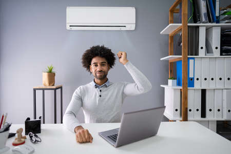 Young Businessman Operating Air Conditioner With Remote Controller In Office
