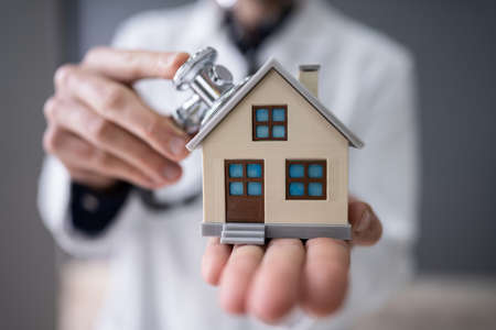 Close-up Of A Doctor's Hand Holding Stethoscope On House Model