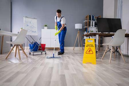 Close-up Of Man Cleaning The Floor With Yellow Wet Floor Sign Foto de archivo - 134609464
