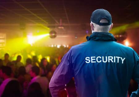 Mannelijke beveiligingsbeambte met een pet die in de nachtclub staat met zijn handen op de heupen