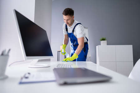 Portrait Of Happy Young Maid Cleaning Glass Table In Office Foto de archivo - 134609562