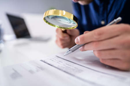 Close-up Of A Businessperson's Hand Looking At Receipts Through Magnifying Glass At Workplace Reklamní fotografie