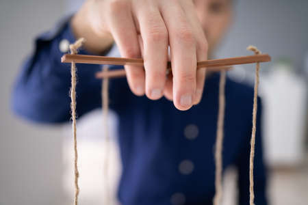 Close-up Of A Businessperson's Hand Manipulating Marionette With String